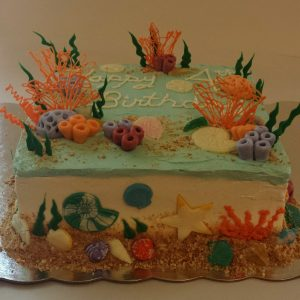 under the sea birthday cake with fondant coral, green chocolate seaweed, and chocolate shells