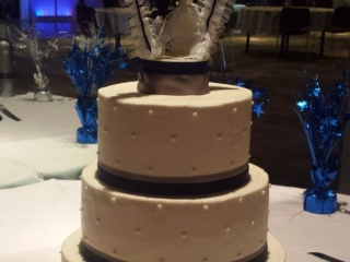 simple white wedding cake with swiss dot and navy ribbon