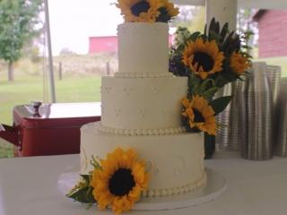 Elegant white-on-white wedding cake with fresh sunflowers.