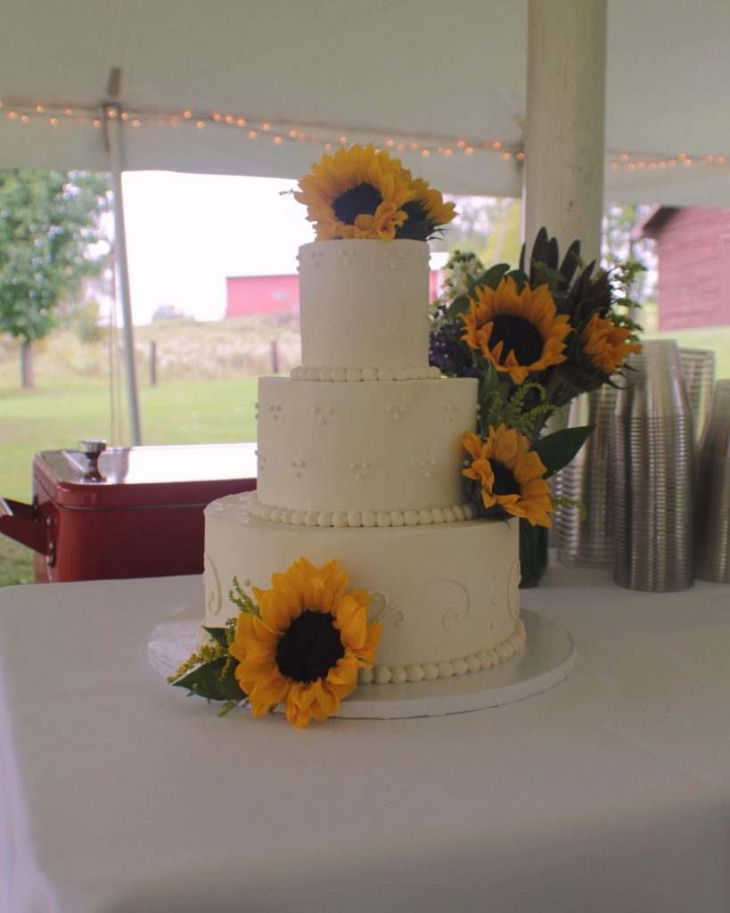 Elegant white-on-white wedding cake with fresh sunflowers.