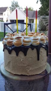 S'mores cake with graham cracker buttercream, topped with chocolate ganache drip and toasted meringue.