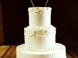 White wedding cake, three tiers, with white buttercream scroll work and hand made twisted wire cake topper.