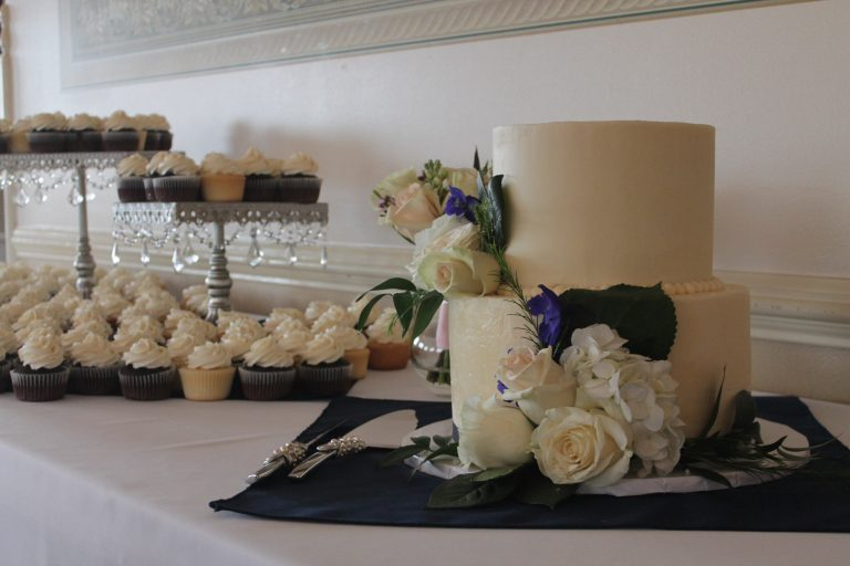 Simple white wedding cake with flower adornments of blush roses, hydrangea, and deep blue columbine along with 15 dozen vanilla and chocolate cupcakes frosted with vanilla buttercream.