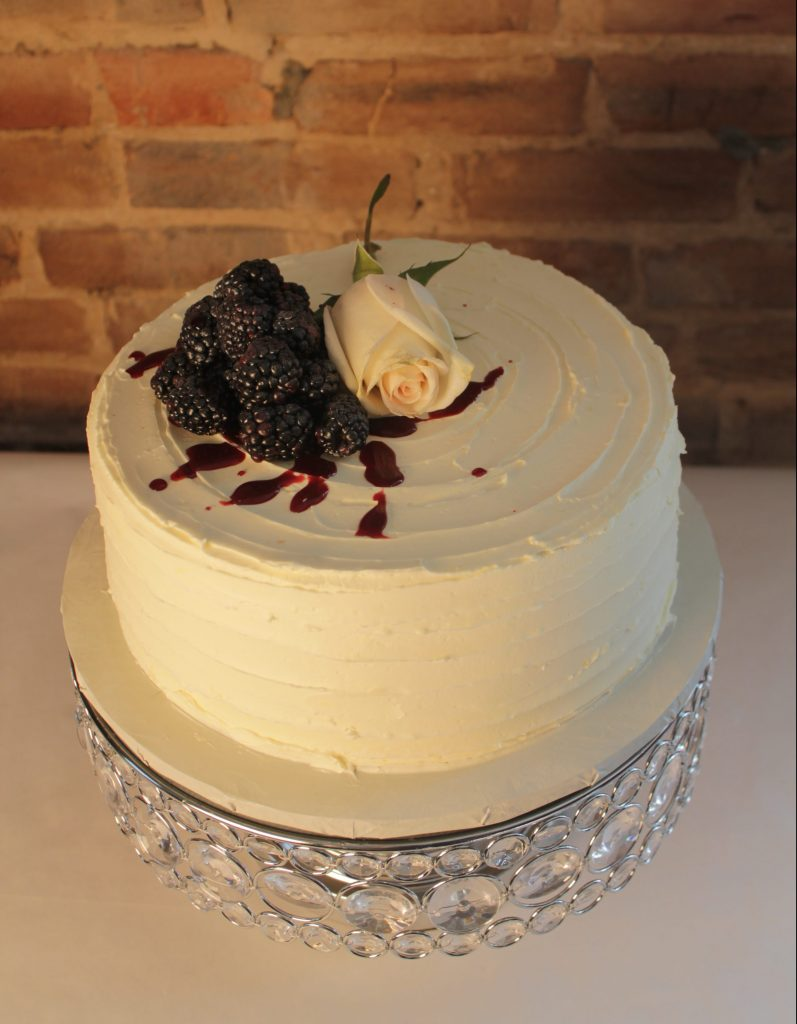 Vanilla Bean Cake with Blackberry Creme filling and Lemon Curd Swiss Meringue Buttercream topped with a blush pink rose and juicy blackberries and blackberry syrup.