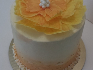 Orange watercolor-style frosted birthday cake with large orange-yellow chocolate flower decoration.