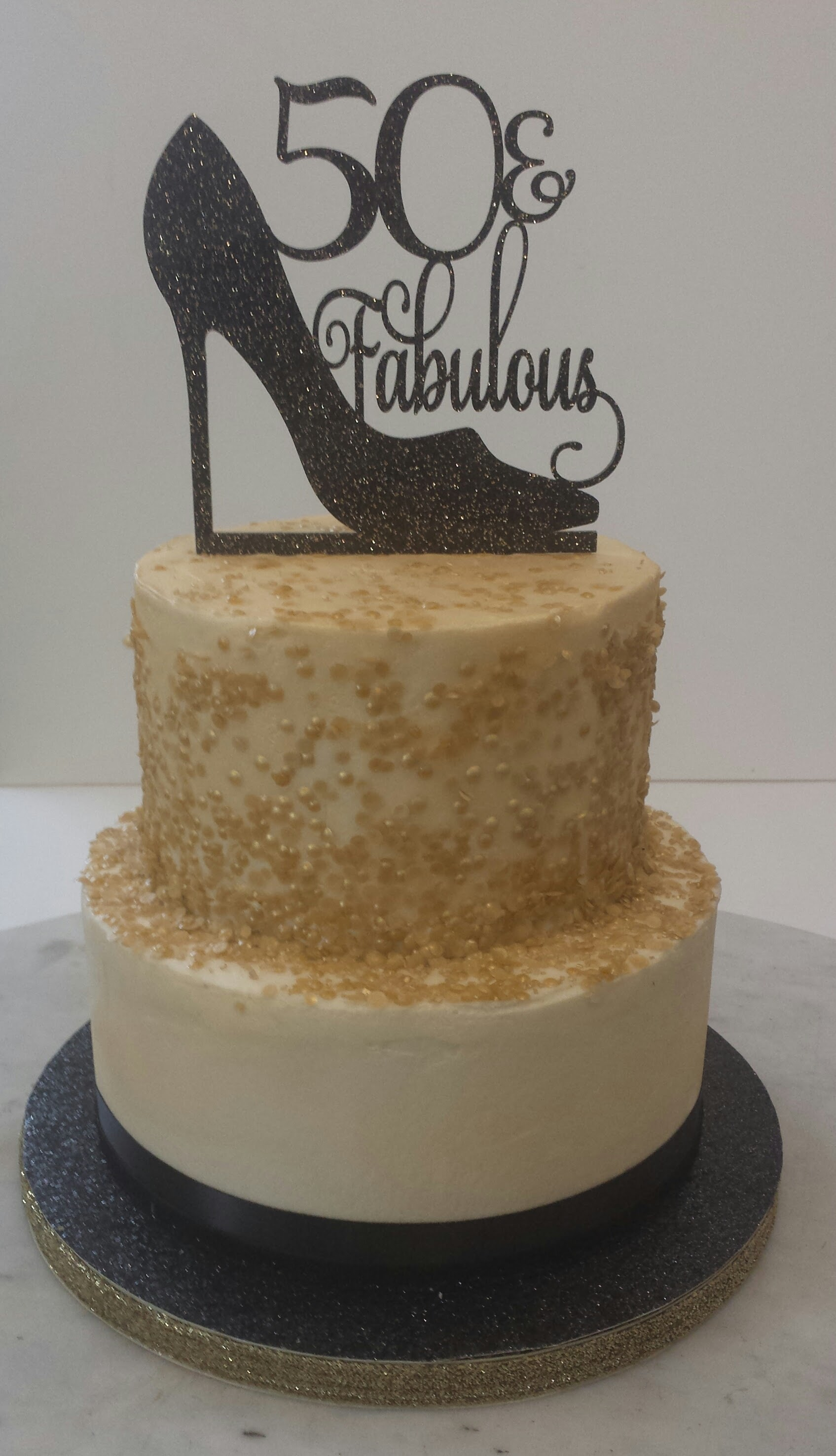 Two-tier vanilla birthday cake with edible gold sequins and a fabulous cake topper.