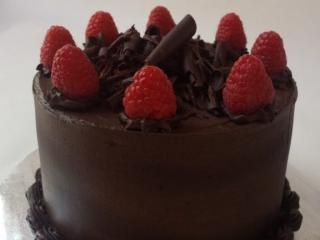 Dark chocolate birthday cake with dark chocolate buttercream topped with fresh raspberries and chocolate curls.
