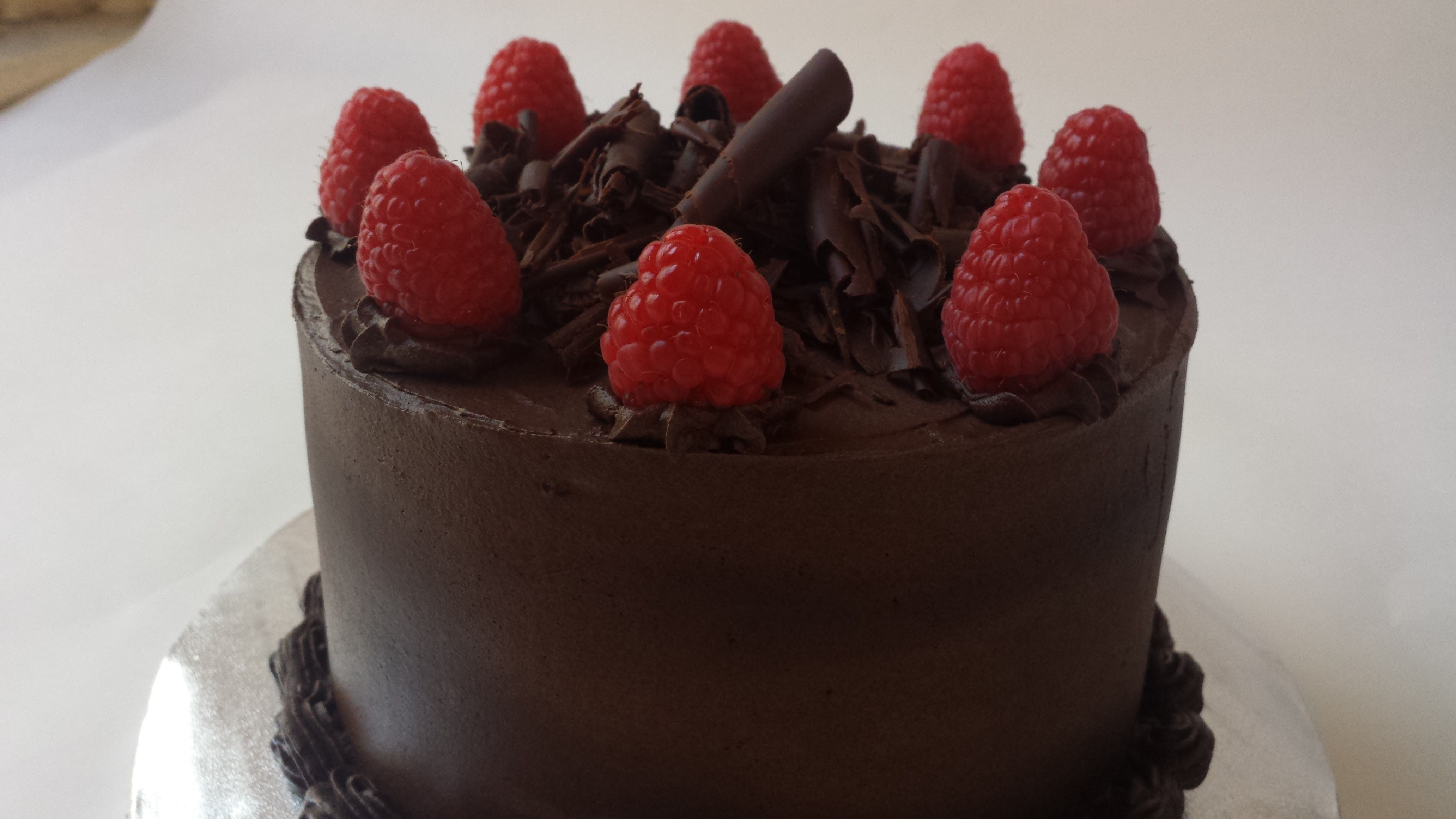 Dark chocolate birthday cake with dark chocolate buttercream topped with fresh raspberries and chocolate curls.