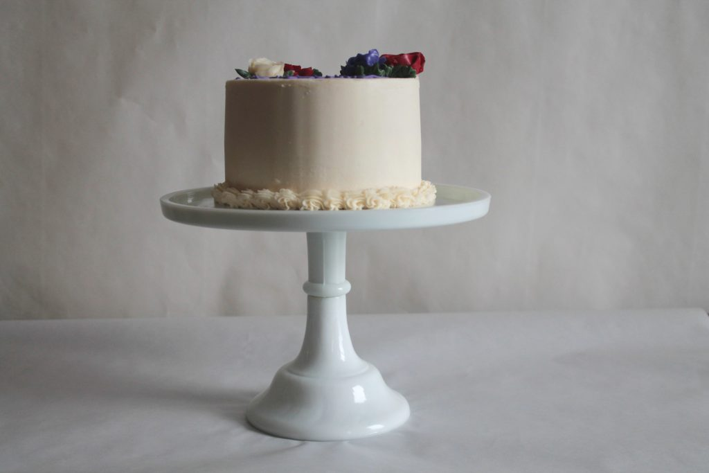 Simple birthday cake with buttercream roses on a white pedestal cake stand.