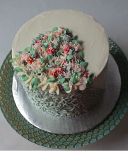 little flowers and swirls on a cake in all buttercream