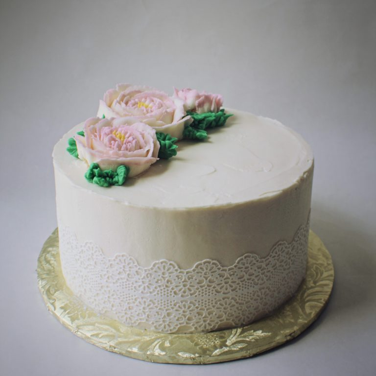Small elegant wedding cake with buttercream cabbage roses and sugar lace.