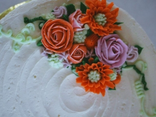 Buttercream piped flowers decorate a cake in oranges, light purple and pink, and green