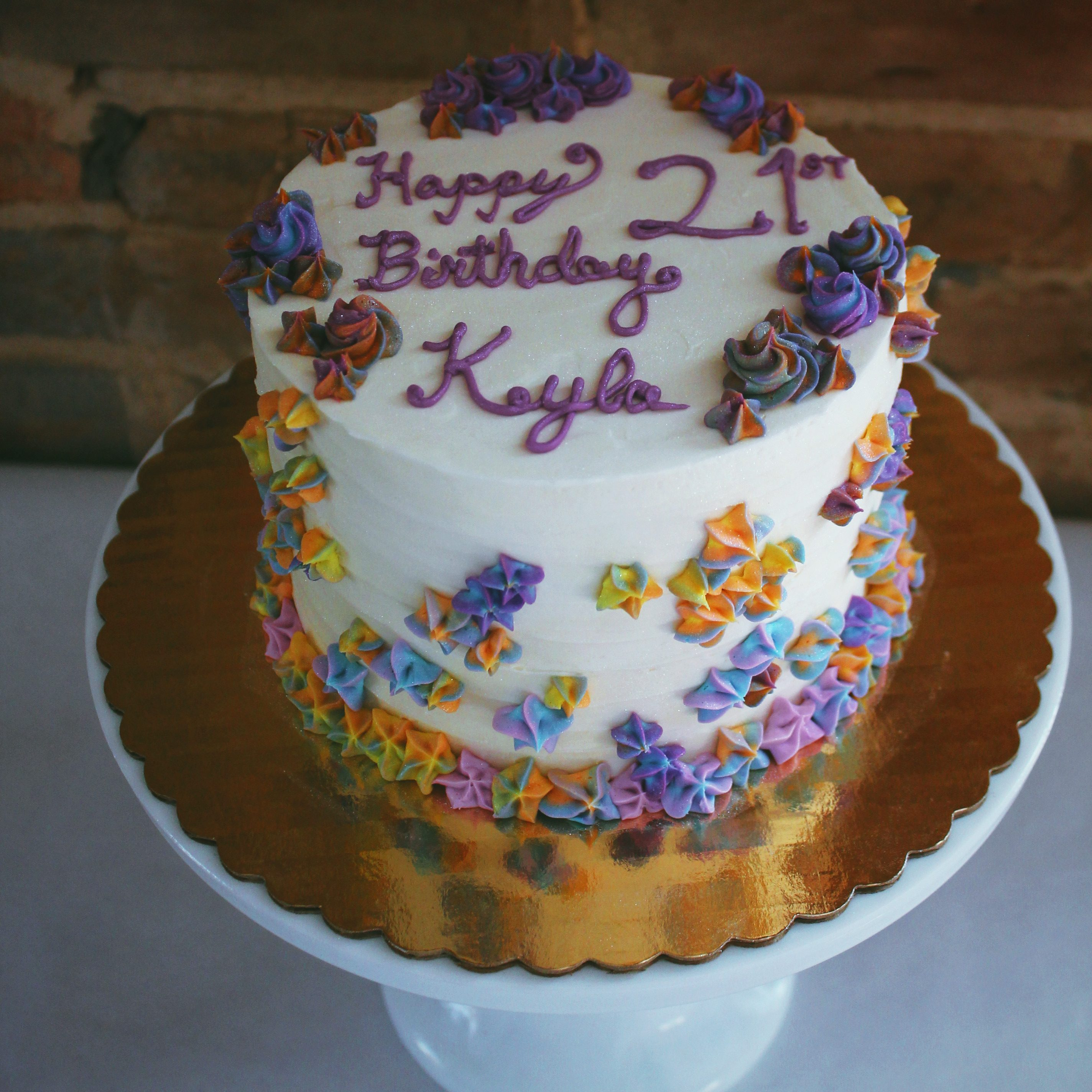 Funfetti birthday cake with multi-colored piped star flowers and rosettes