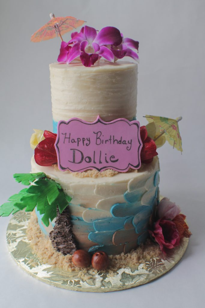 Two-tier tropical theme birthday cake with edible flowers and other decorations