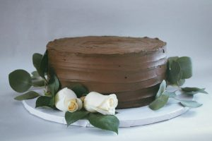 Single tier wedding cake, chocolate cake with swirled chocolate buttercream decorated with white roses and greenery