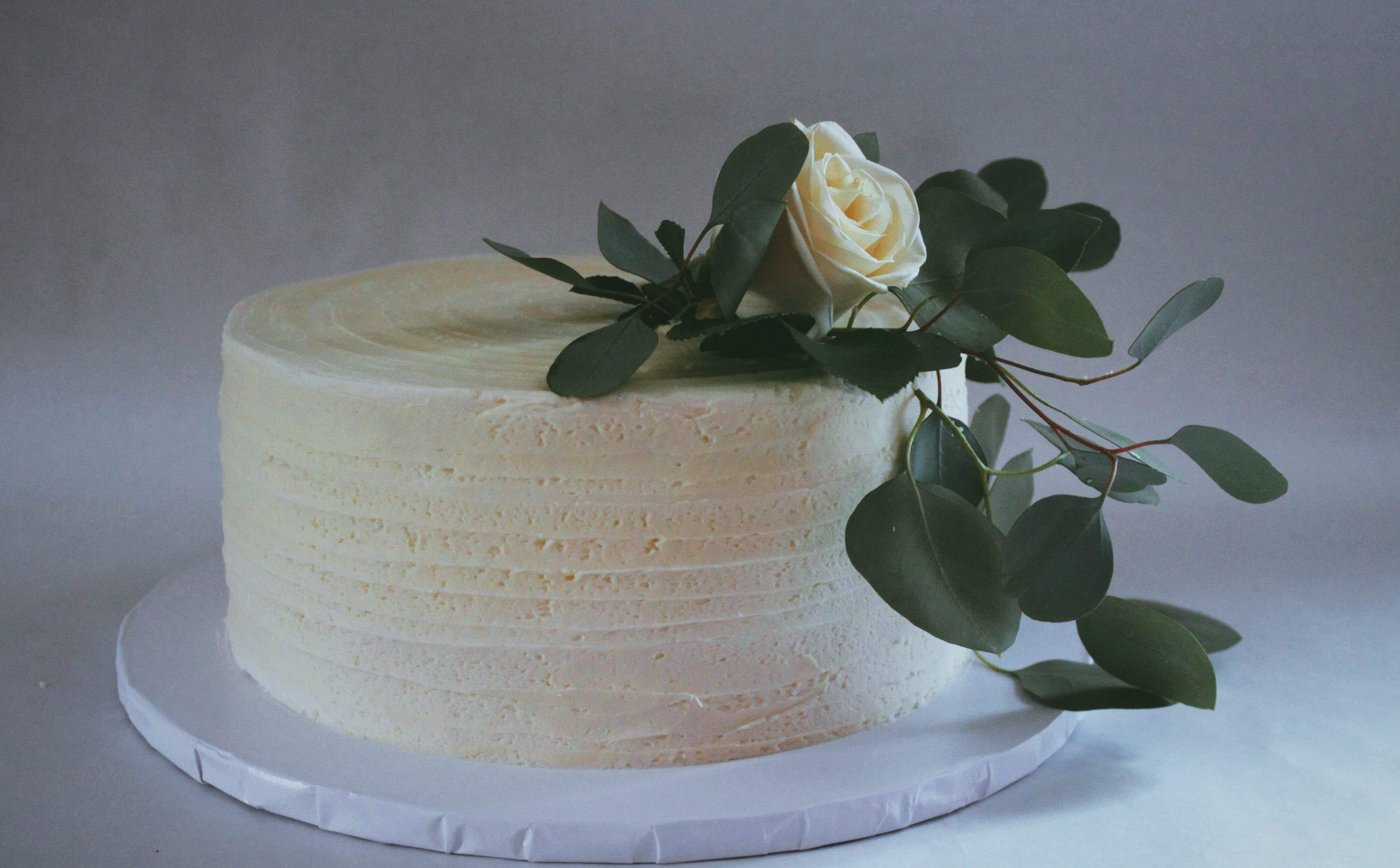 Simple single tier wedding cake with fresh white rose and greens