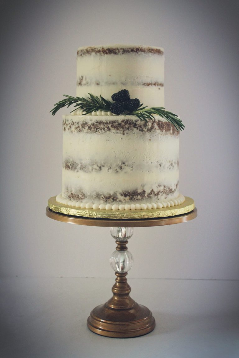 Two tiers of Carrot Cake filled and frosted with Cream Cheese Buttercream garnished with fresh rosemary sprigs and blackberries.