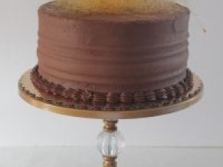 Chocolate Cake with caramel mousse filling and chocolate buttercream frosting topped with sugar strand nest.