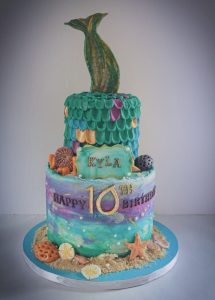 Two tier birthday cake with buttercream watercolored blues and purples, mermaid scales, and mermaid tail topper