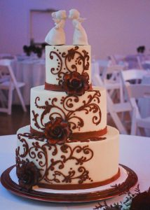 White wedding cake, three tiers, decorated with burgundy piped buttercream scrollwork and burgundy gumpaste floewrs.